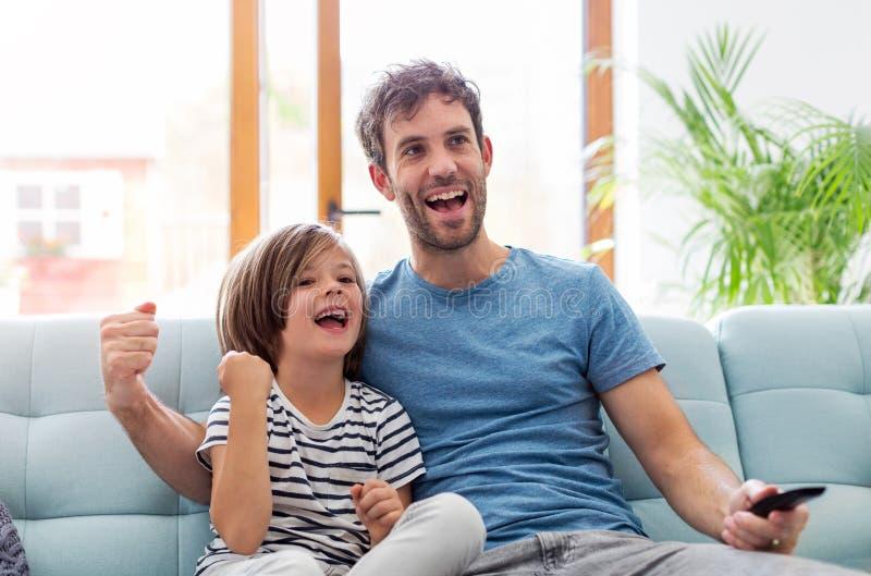 在沙发的父亲和儿子观看的电视 库存图片