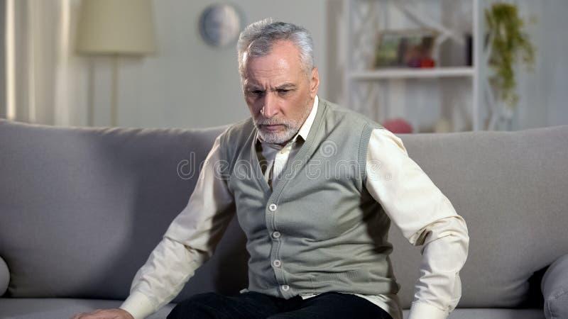 在沙发的资深男性开会,不适的感觉,问题以人健康,疾病 库存照片