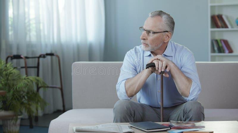 在沙发的退休的男性开会在老人院和考虑生活,悲伤 图库摄影