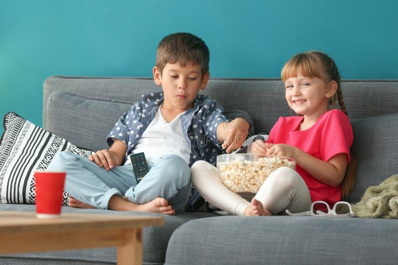 在沙发的逗人喜爱的儿童看着电视在家 免版税库存图片