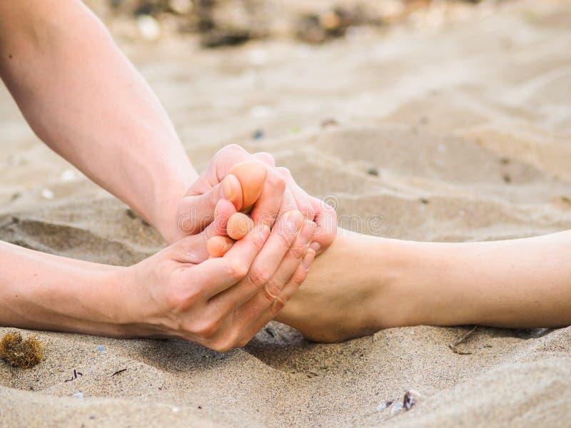 在沙子、男性和女性白种人的脚按摩 免版税库存图片