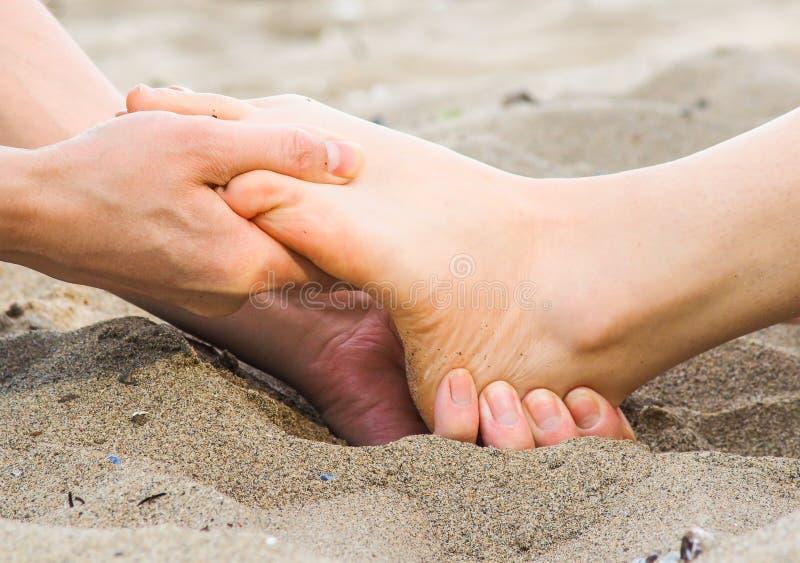 在沙子、男性和女性白种人的脚按摩 库存图片