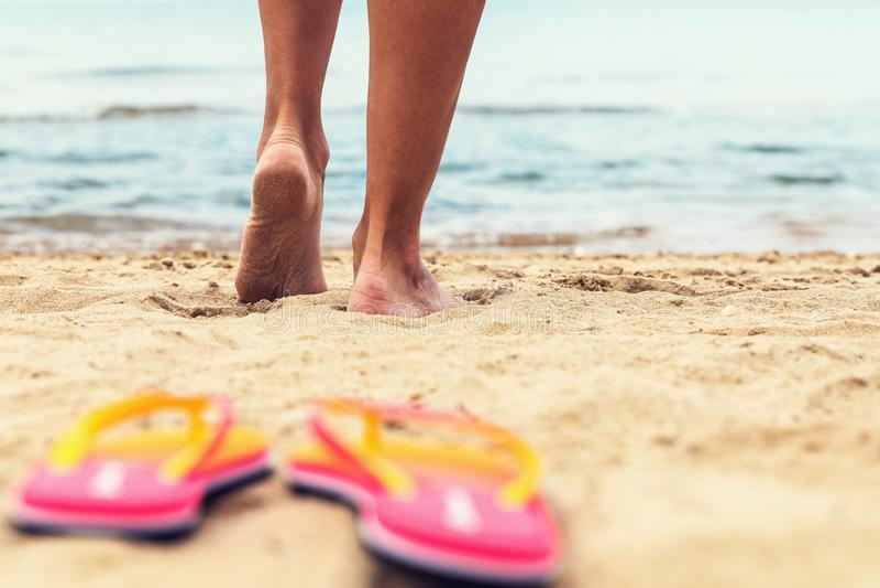 在沙子关闭的脚 女孩去沿海滩的海 库存照片