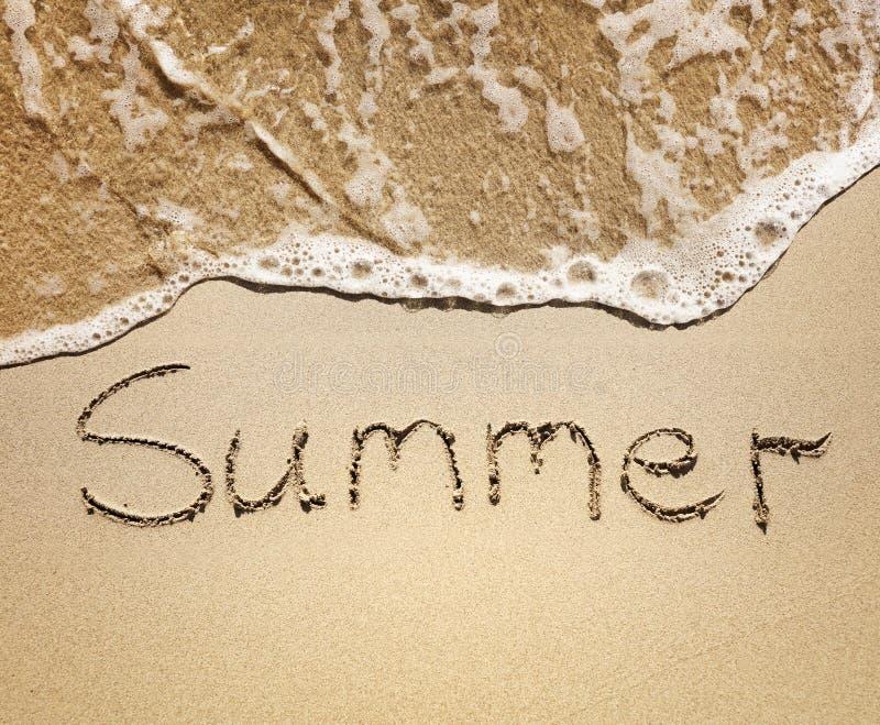 在沙子写的夏天由海挥动 库存照片