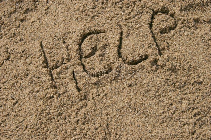 在沙子写的帮助 图库摄影
