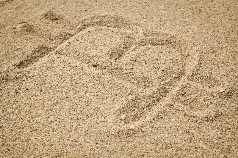 在沙子写的著名cryptocurrency标志 库存照片