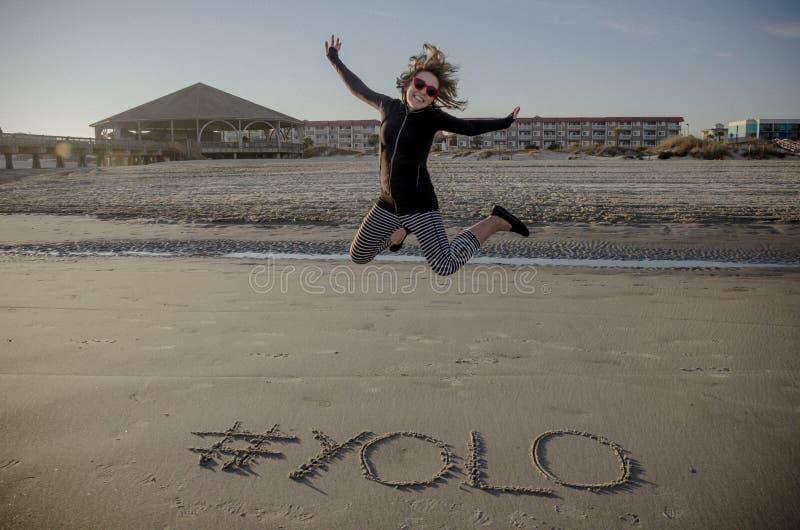在沙子写的YOLO hashtag在海滩和一成年女性跳跃 免版税图库摄影