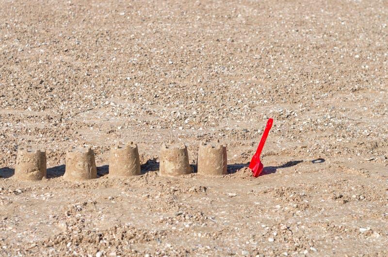 在沙子外面的泥饼以城堡和红色孩子的形式铲起 免版税库存图片