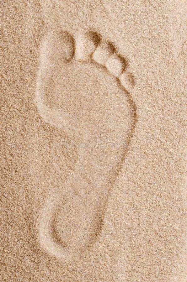 在沙子宏指令照片的脚印 库存图片