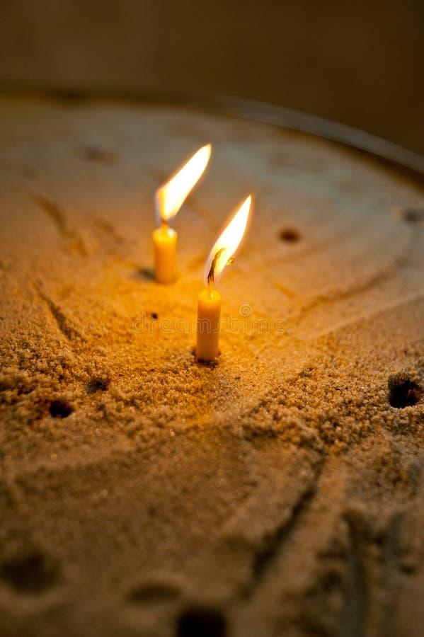 在沙子投入的两个灼烧的蜡蜡烛 免版税库存照片