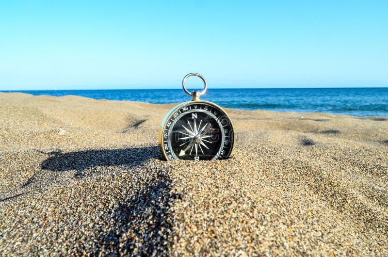 在沙子海滩的指南针 皇族释放例证