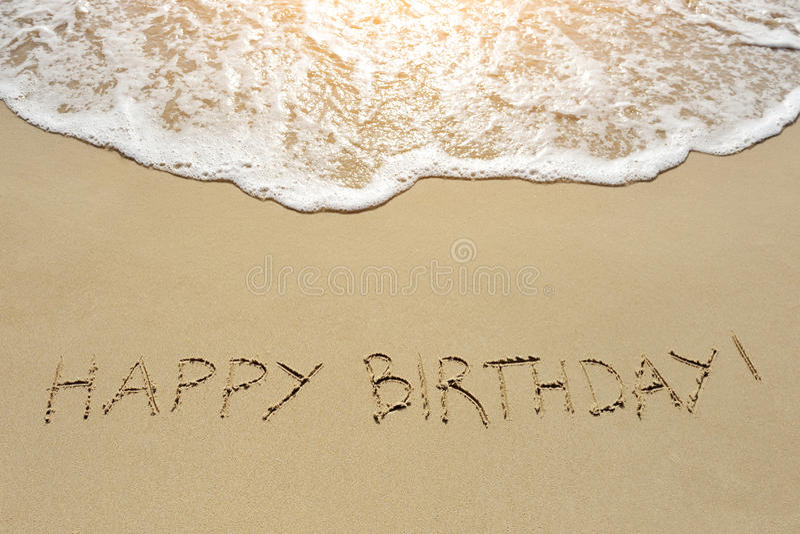 在沙子海滩写的生日快乐 免版税库存照片