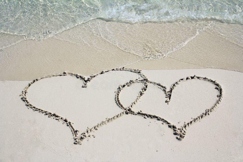 在沙子海滩的两心脏 免版税库存照片