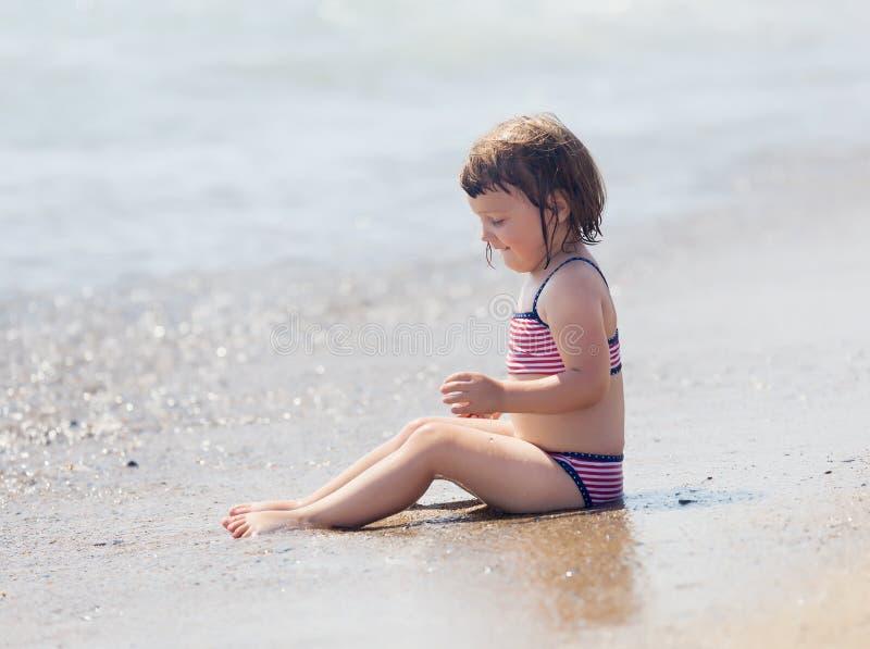 在沙子海滩的女孩选址 免版税库存图片