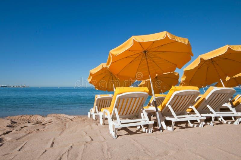 在沙子海滩的明亮的黄色伞 免版税库存图片