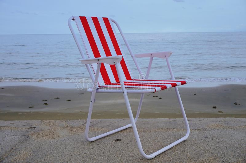 在沙子海滩的红色海滩睡椅 图库摄影