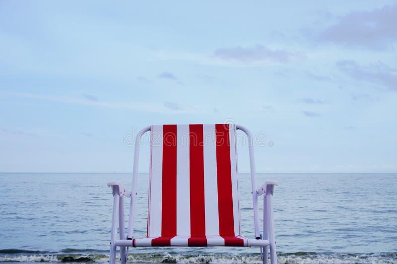 在沙子海滩的红色海滩睡椅 库存照片