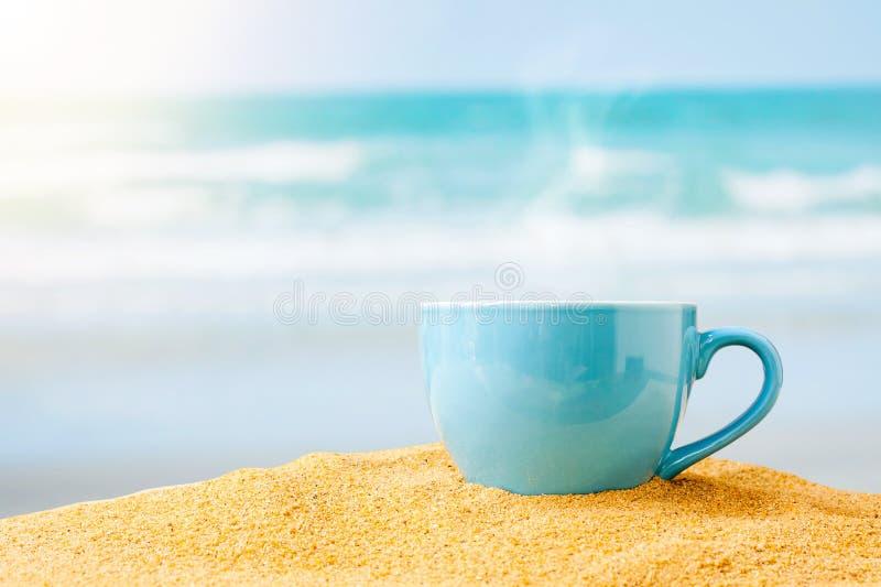 在沙子海滩的蓝色咖啡杯 库存照片
