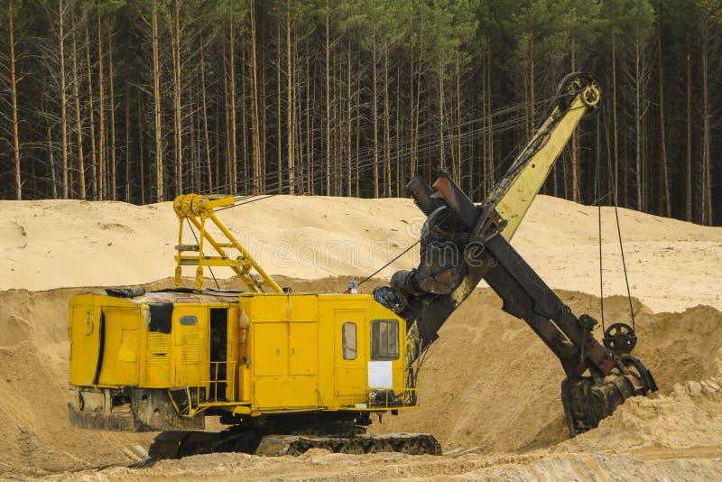 在沙子猎物的挖掘机 大橙色挖掘者在开放沙子矿等待新的转移 图库摄影
