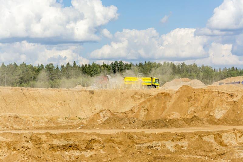 在沙子猎物的明亮的黄色卡车 免版税库存图片