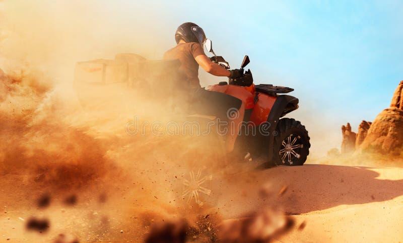 在沙子猎物,尘云,方形字体自行车的Atv骑马 免版税库存照片