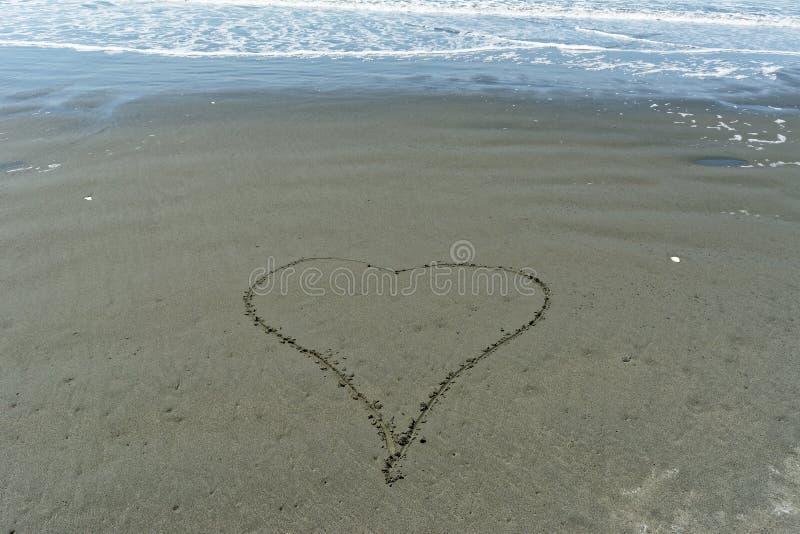 在沙子用手画的单纯化的爱心脏 图库摄影