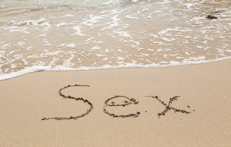 画在沙子由性别字海洋  免版税库存照片