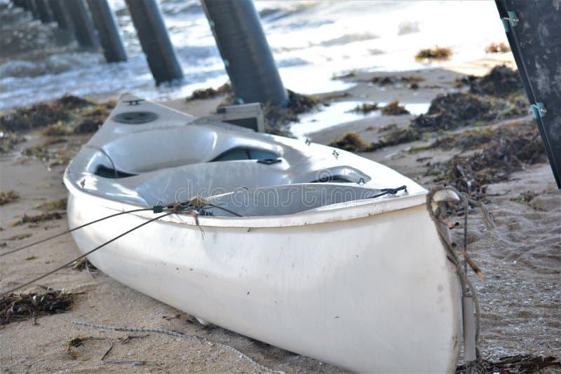 在沙子的一条美丽的白色小船在跳船下 免版税库存图片