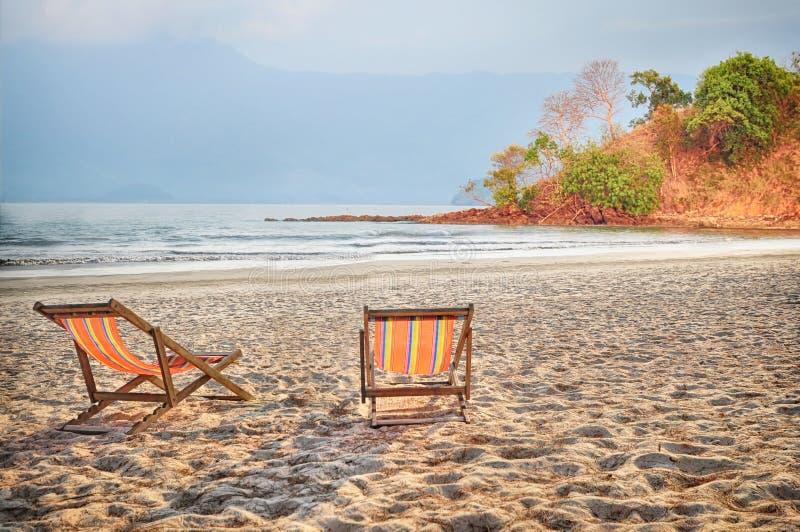 在沙子的两deckchair帆布在热带海滩背景 免版税库存图片