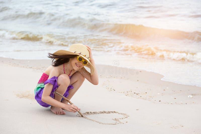 在沙子的亚洲女孩凹道心形,夏天浓缩海滩的爱 免版税库存照片
