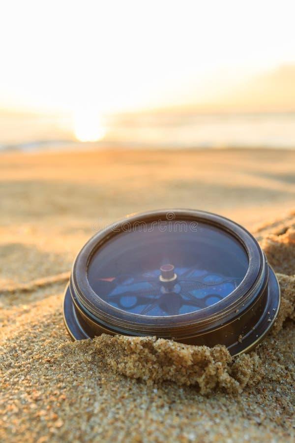 在沙子的古老指南针在海滩日出 库存照片
