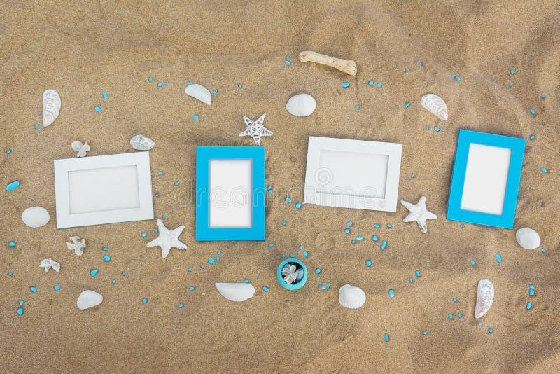 在沙子的四个空白的照片框架靠岸与装饰 免版税库存图片