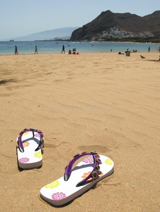 在沙子的塑胶人字平底拖鞋 免版税库存照片