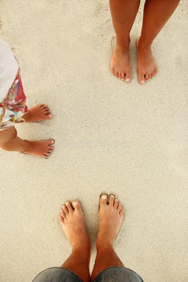 在沙子的家庭脚在海滩 免版税库存图片