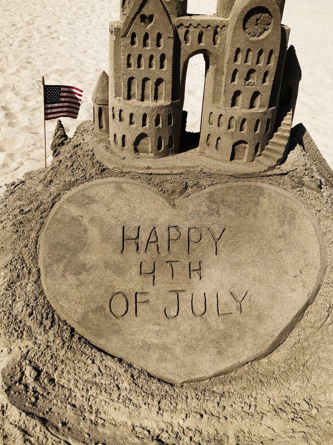 在沙子的愉快的7月4日消息 免版税库存图片