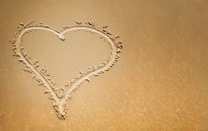在沙子的手指拉长的心脏,爱的标志 库存照片