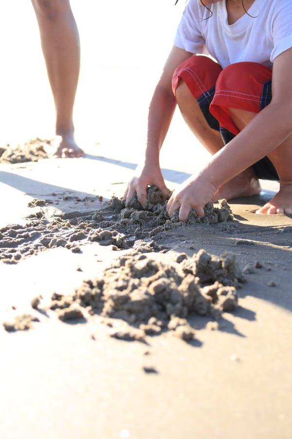 在沙子的手 免版税库存照片