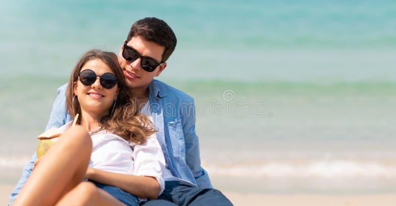 在沙子的放松的年轻开会在与拷贝空间的海滩 免版税库存图片