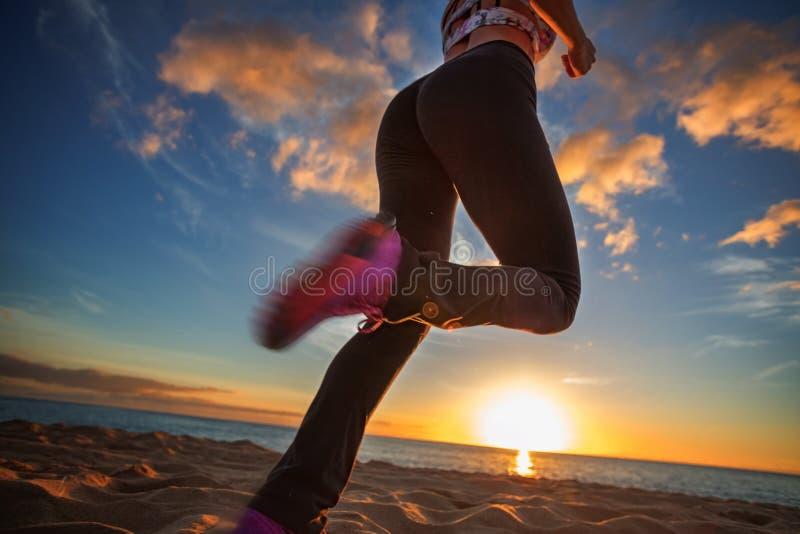 在沙子的日落海滩适合的女孩jogginr反对日落背景 免版税库存图片