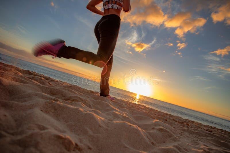 在沙子的日落海滩适合的女孩jogginr反对日落背景 免版税图库摄影