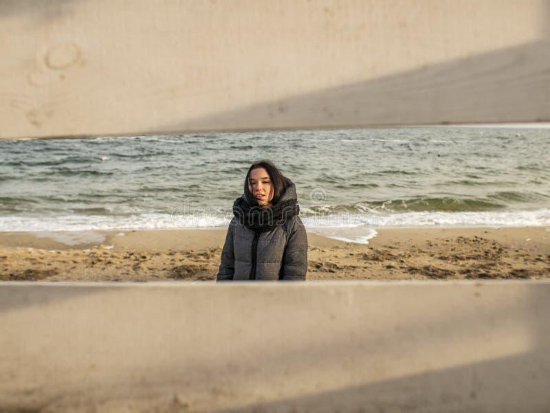 在沙子的有吸引力的少女身分以海为背景 看法通过木篱芭 暗中侦察在女孩 免版税库存照片