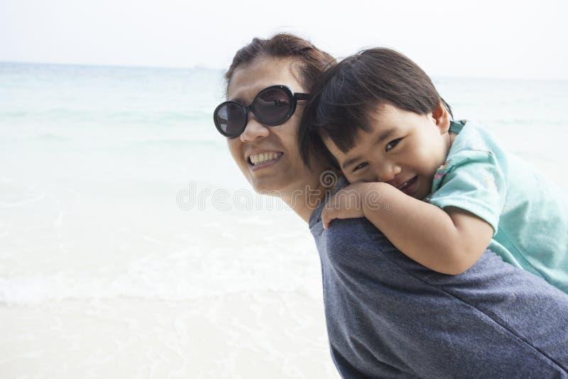 在沙子的母亲和孩子松弛情感靠岸   免版税库存图片