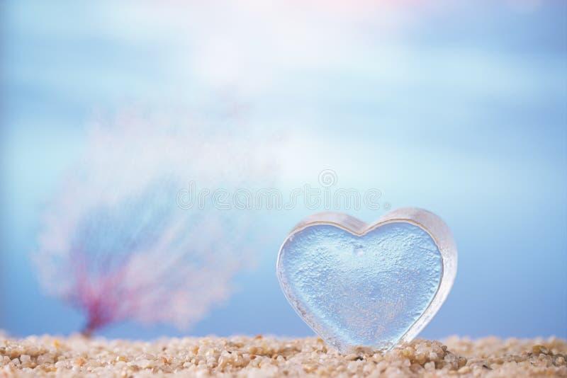 在沙子的清楚的玻璃心脏与热带海洋 库存图片