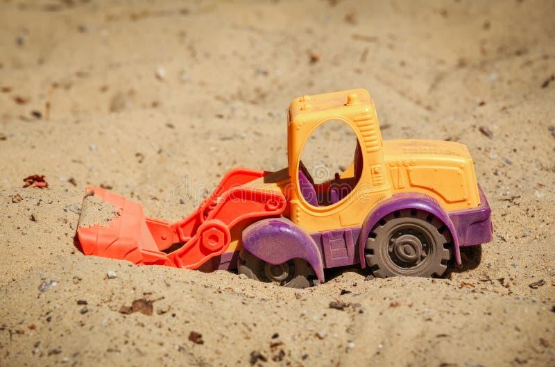 在沙子的玩具推土机 一位小挖掘者 库存图片