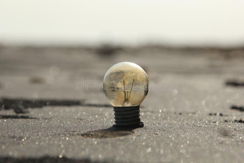 在沙子的电灯泡 库存照片