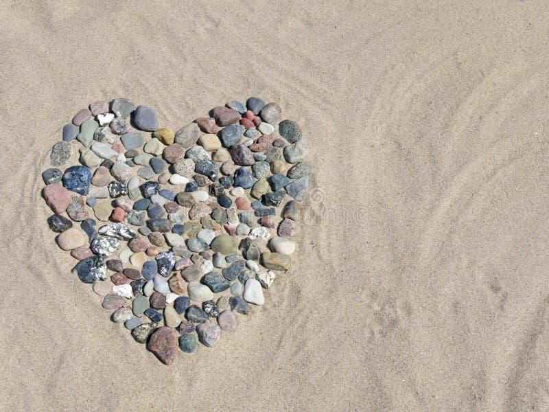 在沙子的石心脏在海滩 免版税库存图片