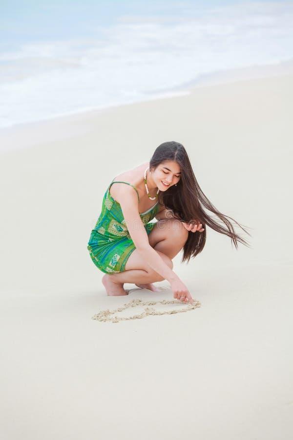 在沙子的美好的青少年的女孩图画心脏在热带海滩 免版税库存图片