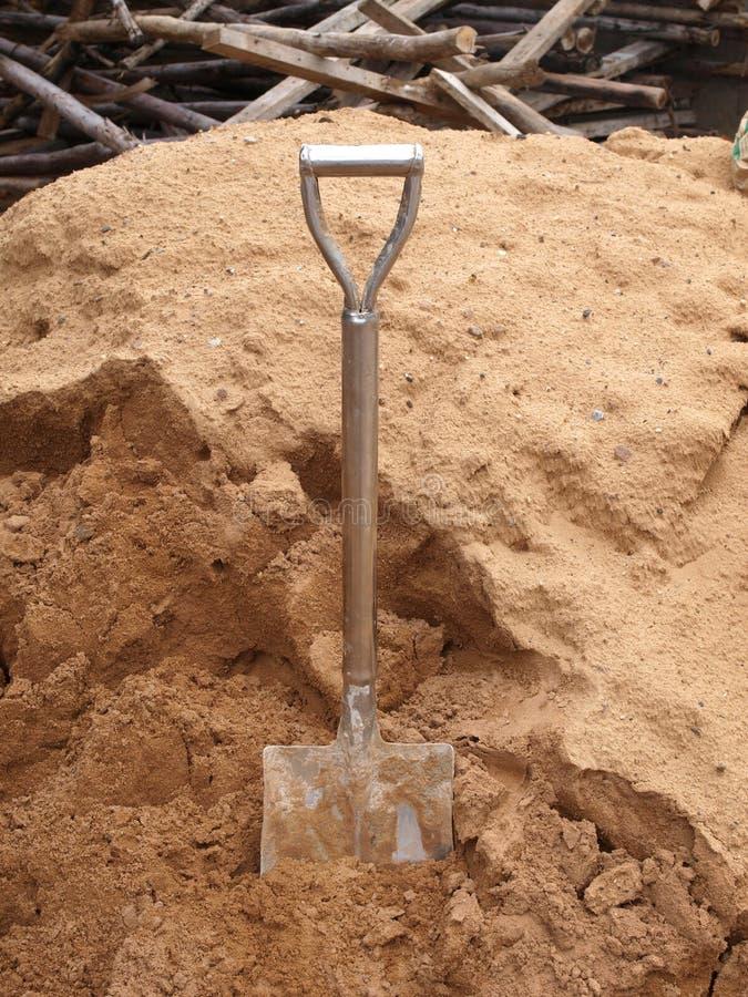 在沙子的老铁锹开掘 免版税图库摄影