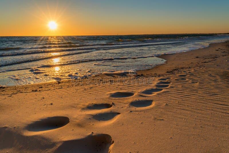 在沙子的脚印在日落 免版税库存照片