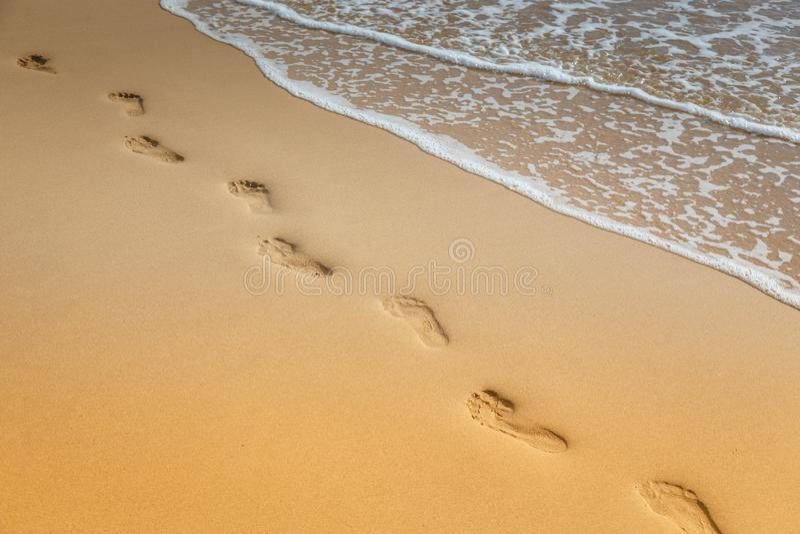 在沙子的脚印在海滩 复制空间 免版税库存图片